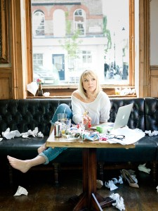 Photo of author Helen Fielding, seated at a cluttered table, surrounded by scraps of paper. Image credit: Pal Hansen